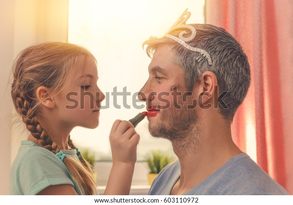 dad with cute daughter beeing treated with lipstick for carnival