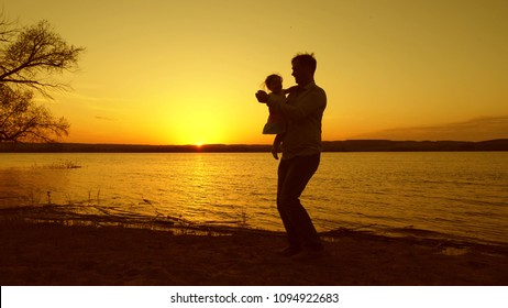Dad dances with his little daughter at sunset against beautiful lake.