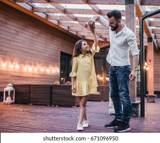 Dad is dancing with his daughter on house's terrace.