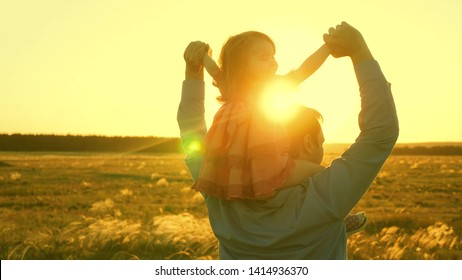 Dad dancing on his shoulders with his daughter in sun. Father travels with baby on his shoulders in rays of sunset. child with parents walks at sunset. happy family resting in park. family concept