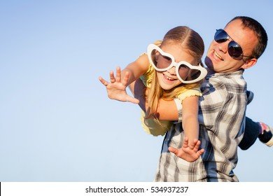 Dad and daughter in big sunglasses playing near a house at the day time. People having fun outdoors. Concept of friendly family.