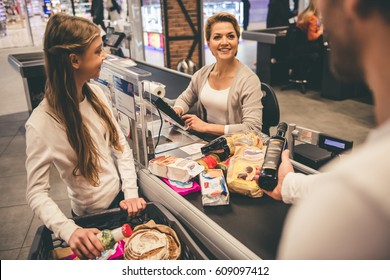 Dad and daughter at the cash desk in supermarket, beautiful cashier is smiling