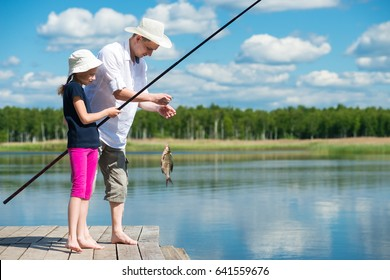 Dad and daughter caught a fish in a bait in the lake