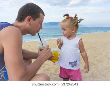 Dad and daughter drinking juice on the beach.