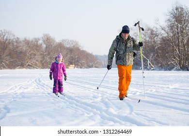Dad and daughter go cross country skiing. Family sport. Sunny day. In the background is a forest.