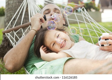 Dad and daughter in a hammock blowing bubbles