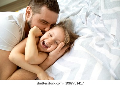 Dad and daughter have fun at home on the bed. Father's Day.