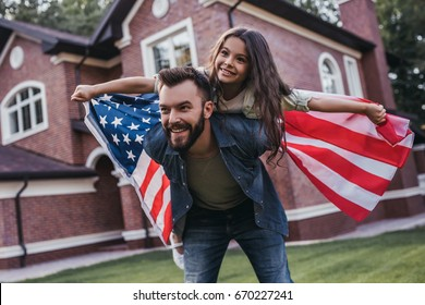 Dad and daughter are having fun on the backyard with american flag in hands and smiling.