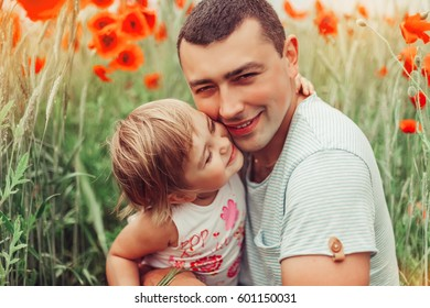 Dad and daughter are hugging and kissing in the fresh air in a good mood in the field of red poppies