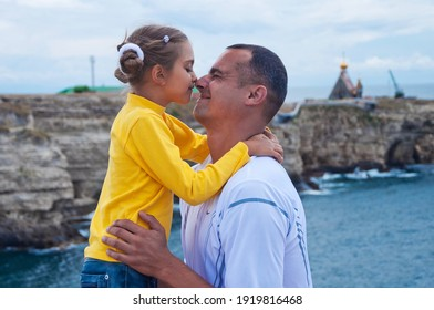 dad and daughter hugging,  dad and little daughter are happy on the background of the sea. family kissing on the background of the sea. dad's love