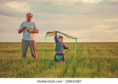 Dad with daughter launch a kite.