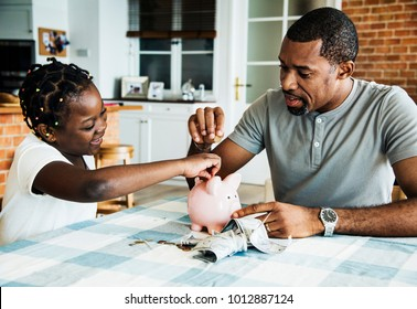 Dad and daughter saving money to piggy bank