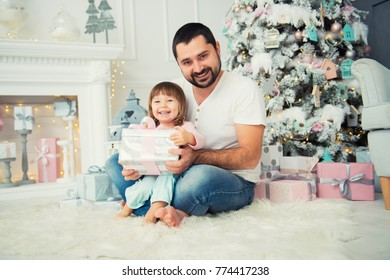 Dad and daughter are sitting and opening a Christmas present near the Christmas tree. Happy New Year