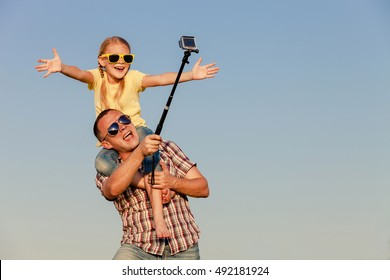 Dad and daughter in sunglasses playing near a house at the day time. People having fun outdoors.  Concept of friendly family.