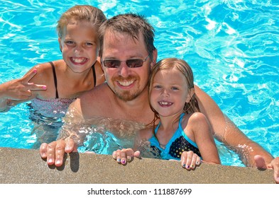 dad with daughters in swimming pool