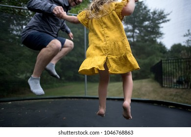 Dad and ddaughter jumping on a trampoline