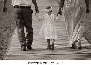 dad in dress pants with belt and white shirt little girl in white dress and white headband and mom in a dress from behind walking on a wooden boardwalk at the beach with sand holding hands together