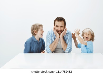 Dad fed up with bad behaviour of sons. Portrait of displeased depressed father sitting at table screaming from depression while children shouting and fooling around, being noisy while mom absent