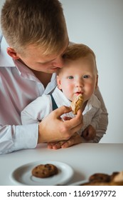 Dad feeds his young son a croissant. father and his son having a delicious breakfast together.