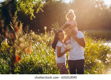 Dad giving daughter piggyback outside. Portrait of a young happy family walking under the sunlight