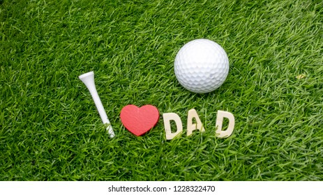 Dad with golf ball and tee with love on green grass