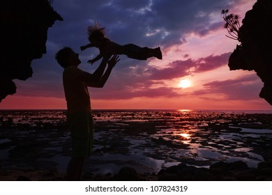 Dad having fun with his son in the sunset