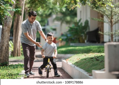 dad help his son learning to ride a bike using balance or push bikecycle
