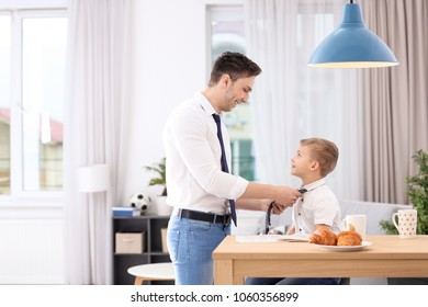 Dad helping his son knot necktie at home
