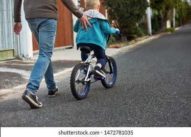 Dad helping son balance on bike, learning how to ride bicycle giving a push on the back