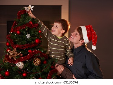 Dad helping son to decorate christmas tree, boy putting up the top ornament, smiling.