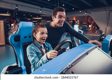 Dad helps little daughter drive a car in games. Little girl smiles while driving a car in a toy machine with the help of her dad.