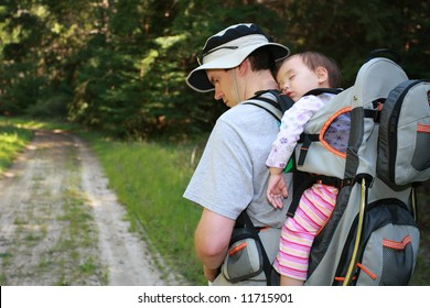 Dad hiking with 16 months old baby girl in carrier