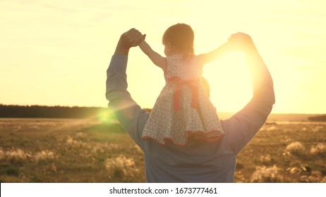 Dad with his beloved daughter on his shoulders dances in flight and laughs. Happy child plays with his father on sunset field. Silhouette of a man and a child. Family and Childhood Concept