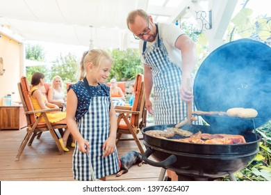 Dad and his daughter doing the barbeque at the grill