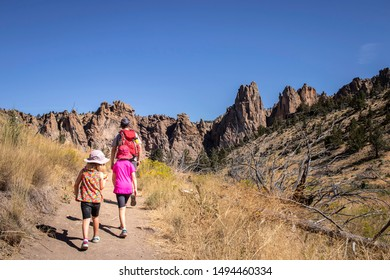 A dad and his daughters hike at Smith Rock State Park along the Wolf Tree trail in   central Oregon.