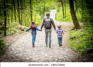 dad with his kids walks from behind in the woods