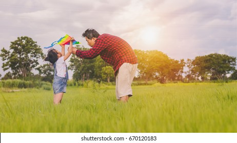 Dad with his little daughter let a kite in a field at the sunset time