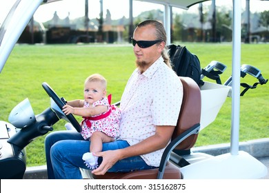 Dad and his little daughters driving golf cart