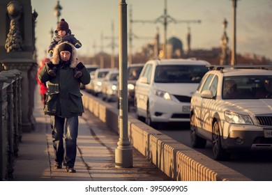 Dad and his son on dads neck  are walking on Troitskiy bridge during a traffic jam in spring Saint-Petersburg, Russia. Image with selective focus and toning