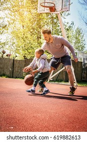 Dad and his son playing basketball.