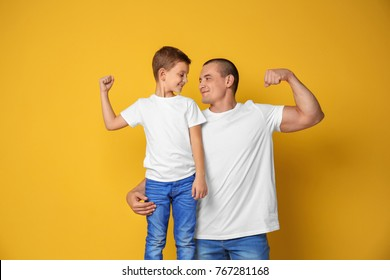 Dad and his son showing muscles on color background