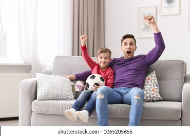 Dad and his son watching football at home