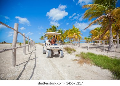 Dad with his two daughters driving golf cart in the palm grove