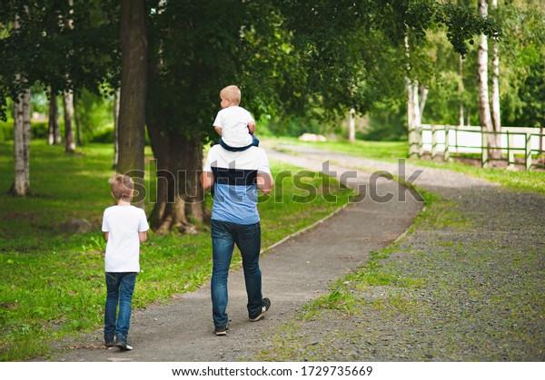 Papa und seine beiden Söhne laufen auf der Straße
