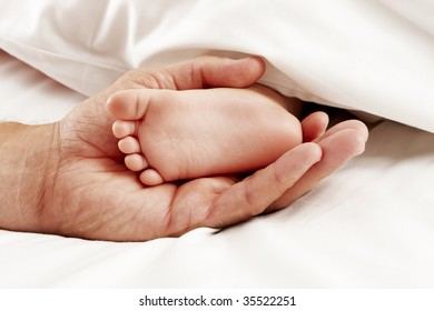 Dad holding baby feet in white sheet