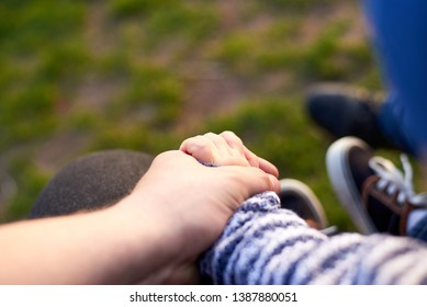 Dad is holding the hand of his little son outdoors, parental love concept