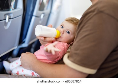 Dad holding his baby daughter during flight on airplane going on vacations. Baby girl drinking formula milk from bottle. Air travel with baby, child and family concept.