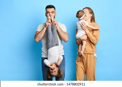 dad holding his child upside down and kissing her feet, while his wife kissing baby on cheek. isolated blue background. studio shot