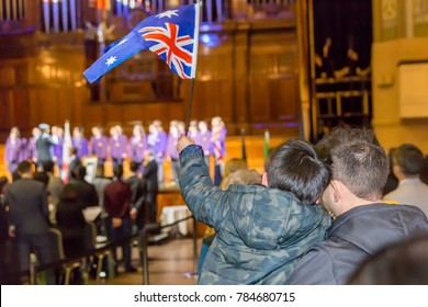 Dad holding his child waving an Australian flag during an Australian citizenship ceremony.