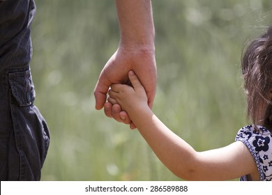 Dad holding his little girl's hand with nature at background.